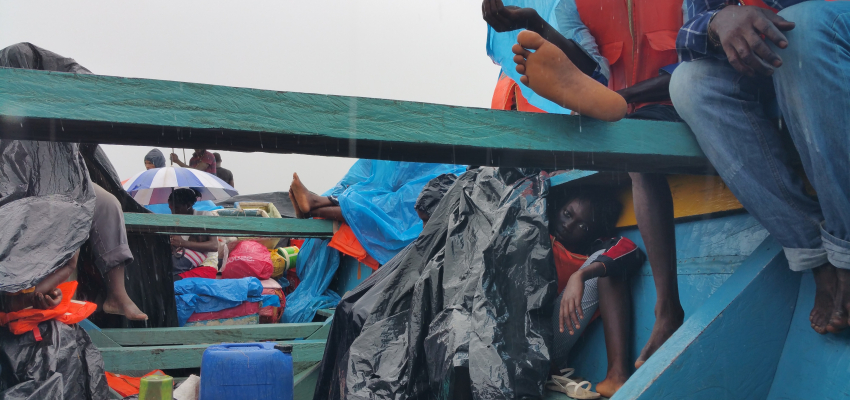 View of refugees from inside the bottom of a small, blue wooden boat