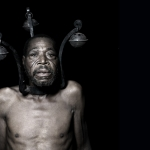 A black man faces the camera, shirtless, head and neck encaged in a metal device with 3 prongs, each with an orb hanging from it.