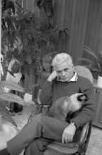 Jacques Derrida sitting in a chair with a cat on his lap