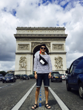Man in sunglasses, navy/white striped long-sleeved shirt and knee-length jean shorts stands on the center divider of the road leading to the Arc de Triomphe, which perspective makes to appear that he is filling the archway.