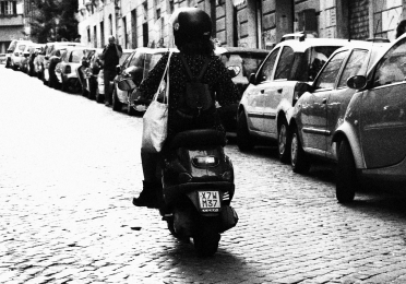 person riding a moped in rome