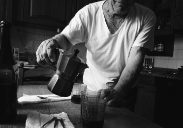 Black and white image of an older man pouring wine from a coffee percolator