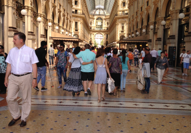 Tourists walking inside under the high ceilings of Galleria vittorio