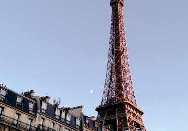 Daytime photo of the Eiffel Tower standing right of center frame, with the half moon as a folcal point.