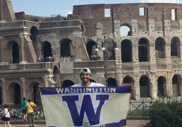 Man with backwards baseball cap holds up UW flag standing in front of the Colosseum in Rome, Italy.