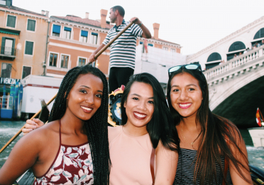 Three women in their 20s huddle for a photograph together as they ride a gondola in Venice, Italy. The gondolier is in the background above them, paddling.