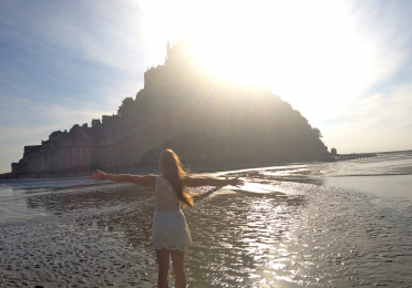 Young woman on the shores below Mon St. Michel