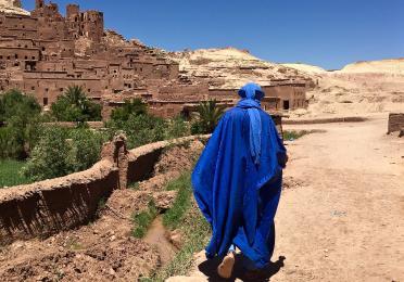 Person walking across Morocco in a bright blue Muslim dress