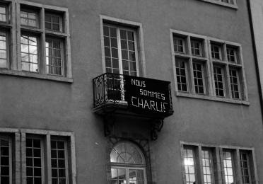 """Sign hanging from Paris balcony, """"We are Charlie"""" in French."""