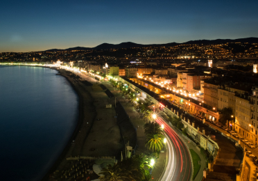 Aerial view of the Promenade Des Anglais in Nice, France at dusk. The photo is a timelapse, turning the traffic on the street into streaks of white and red light.
