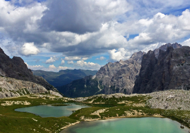View down a valley in the Dolomite Mountains with blue-green glacial ponds in the foreground.