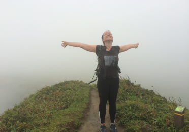 Woman standing atop misty summit of Mt. Pele, arms outstretched