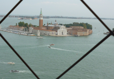 Buildings in Venice, shot through a chain link fence