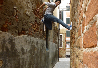 20-some-year-old man shimming up in narrow alley between two Venetian buildings