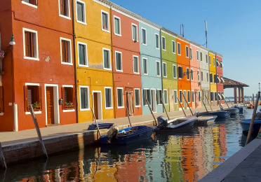Colorful row houses along a canal in Burano, Italy