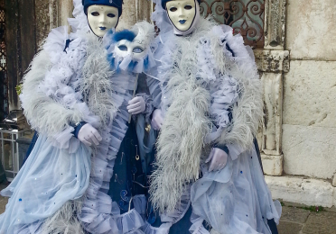 Two people dressed in tall blue hats, porcelain white mask, and frilly frocks pose for a portrait at Carnevale in Venice Italy