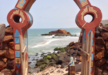 View through a red clay arch with mosaic tile, looking in to a rocky beach with waves crashing.