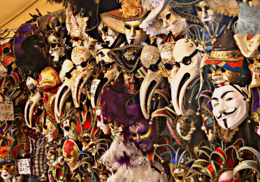 A wall of Carnevale masks hung on a wall in Venice Italy. There are so many masks they are piled atop one another, with only elongated noses sticking out.