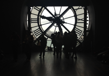 Backlit photo from inside the clock tower of the Musée d'Orsay, with peoples' silouhettes milling about infront of the backward clockface