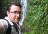 Selfie of Mathew in front of waterfall