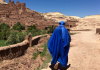 Person walking across Morocco in a bright blue Muslim dress